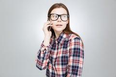 Adolescente precioso lindo en vidrios que habla en el teléfono celular Fotos de archivo libres de regalías