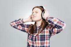 Adolescente precioso lindo que escucha la música en auriculares Imágenes de archivo libres de regalías