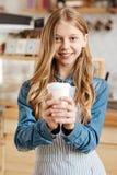 Adolescente precioso que presenta con una taza de café Imagen de archivo libre de regalías