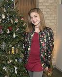 Adolescente precioso que se coloca delante de un árbol de navidad Fotos de archivo libres de regalías