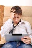 Adolescente preocupado con la tableta Imagen de archivo