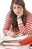 Adolescente preocupante con las pilas de libros de escuela Foto de archivo