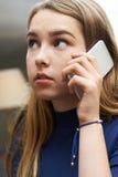 Adolescente preocupante que hace llamada en el teléfono móvil Fotos de archivo
