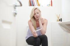 Adolescente preocupante que se sienta en cuarto de baño con la prueba de embarazo Foto de archivo