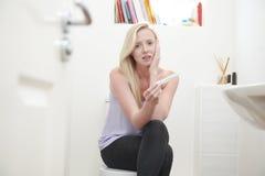 Adolescente preocupante que se sienta en cuarto de baño con la prueba de embarazo Fotografía de archivo