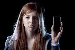 Adolescente preocupante que sostiene el teléfono móvil como la víctima acechada que tiranizaba cibernética de Internet abusó Imagen de archivo libre de regalías
