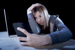 Adolescente preocupante que usa el teléfono móvil y el ordenador como la víctima acechada que tiranizaba cibernética de Internet  Imagen de archivo libre de regalías