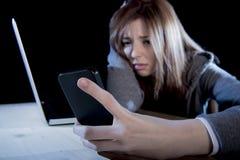 Adolescente preocupante que usa el teléfono móvil y el ordenador como la víctima acechada que tiranizaba cibernética de Internet  Imágenes de archivo libres de regalías