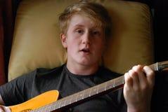Adolescente principal y de los hombros que toca la guitarra Foto de archivo