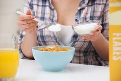 Adolescente que añade a Sugar To Breakfast Cereal Imágenes de archivo libres de regalías