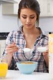 Adolescente que añade a Sugar To Breakfast Cereal Fotografía de archivo libre de regalías