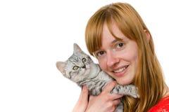 Adolescente que abraza el gato de gato atigrado joven Imágenes de archivo libres de regalías