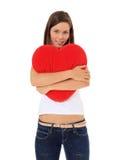 Adolescente que abraza la almohadilla en forma de corazón Foto de archivo