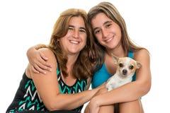 Adolescente que abraza su madre y su pequeño perro Fotos de archivo libres de regalías