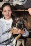 Adolescente que abraza su perro Foto de archivo libre de regalías