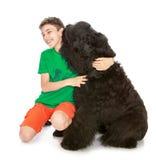 Adolescente que abraza un perro Foto de archivo libre de regalías