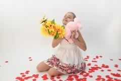 Adolescente que abraza un regalo del día del ` s de la tarjeta del día de San Valentín y un manojo de flores Fotografía de archivo libre de regalías