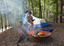Adolescente que acampa com fogo do acampamento imagens de stock royalty free