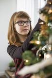 Adolescente que adorna el árbol de navidad en casa Imagen de archivo