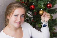 Adolescente que adorna el árbol del Año Nuevo Fotos de archivo libres de regalías