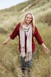 Adolescente que anda através das dunas de areia Fotografia de Stock Royalty Free