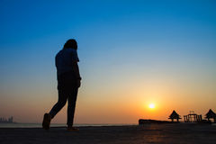 Adolescente que anda em uma ponte que estende no mar no sunse fotos de stock