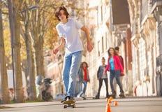 Adolescente que anda en monopatín en el paseo lateral de la ciudad Fotos de archivo