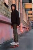 Adolescente que anda en monopatín en la calle de la ciudad en la puesta del sol Fotografía de archivo libre de regalías