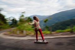 Adolescente que anda en monopatín en montañas Fotos de archivo libres de regalías