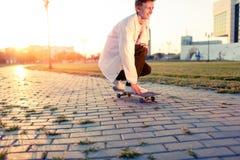 Adolescente que anda en monopatín en un parque en un día libre en tiempo soleado Fotografía de archivo