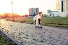 Adolescente que anda en monopatín en un parque en un día libre en tiempo soleado Foto de archivo libre de regalías