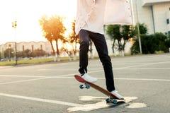 Adolescente que anda en monopatín en un parque en un día libre en tiempo soleado Imágenes de archivo libres de regalías