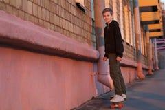 Adolescente que anda en monopatín que monta a la derecha en la calle de la ciudad de la puesta del sol Imágenes de archivo libres de regalías