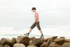 Adolescente que anda a trancos a través de rocas Imágenes de archivo libres de regalías