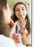 Adolescente que aplica el lápiz labial Foto de archivo libre de regalías