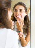 Adolescente que aplica el lápiz labial Imagenes de archivo