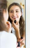 Adolescente que aplica el lápiz labial Imagen de archivo