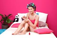 Adolescente que aplica el pulimento de clavo rojo en sus clavos Imagen de archivo libre de regalías
