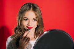 Adolescente que aplica maquillaje Imagen de archivo libre de regalías