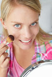 Adolescente que aplica maquillaje Imágenes de archivo libres de regalías