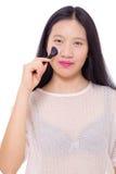 Adolescente que aplica maquillaje con un cepillo Foto de archivo libre de regalías