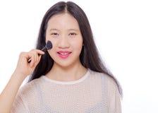 Adolescente que aplica maquillaje con un cepillo Imagen de archivo libre de regalías