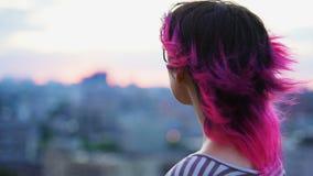 Adolescente que aprecia o por do sol no fundo do scape da cidade, no cabelo cor-de-rosa e nos vidros filme