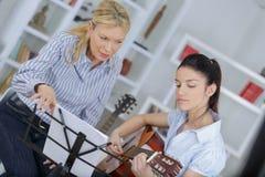 Adolescente que aprende tocar la guitarra Foto de archivo libre de regalías