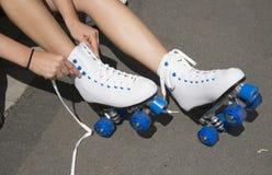 Adolescente que ata cordones en un par de pcteres de ruedas Fotografía de archivo
