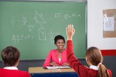 Adolescente que aumenta la mano mientras que profesor Looking At Fotografía de archivo