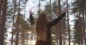 Adolescente que aumenta las manos en concepto de la libertad del bosque del pino del invierno Imagen de archivo libre de regalías