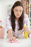 Adolescente que ayuda con la limpieza en casa Foto de archivo libre de regalías
