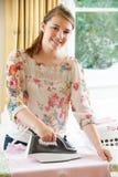 Adolescente que ayuda con planchar en casa Imagen de archivo libre de regalías