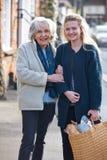 Adolescente que ayuda a la mujer mayor a Carry Shopping Imagen de archivo libre de regalías